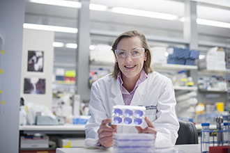 Professor Gabrielle Belz in laboratory holding experimental equipment, smiling at camera